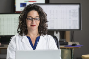 Health professional entering data into computer