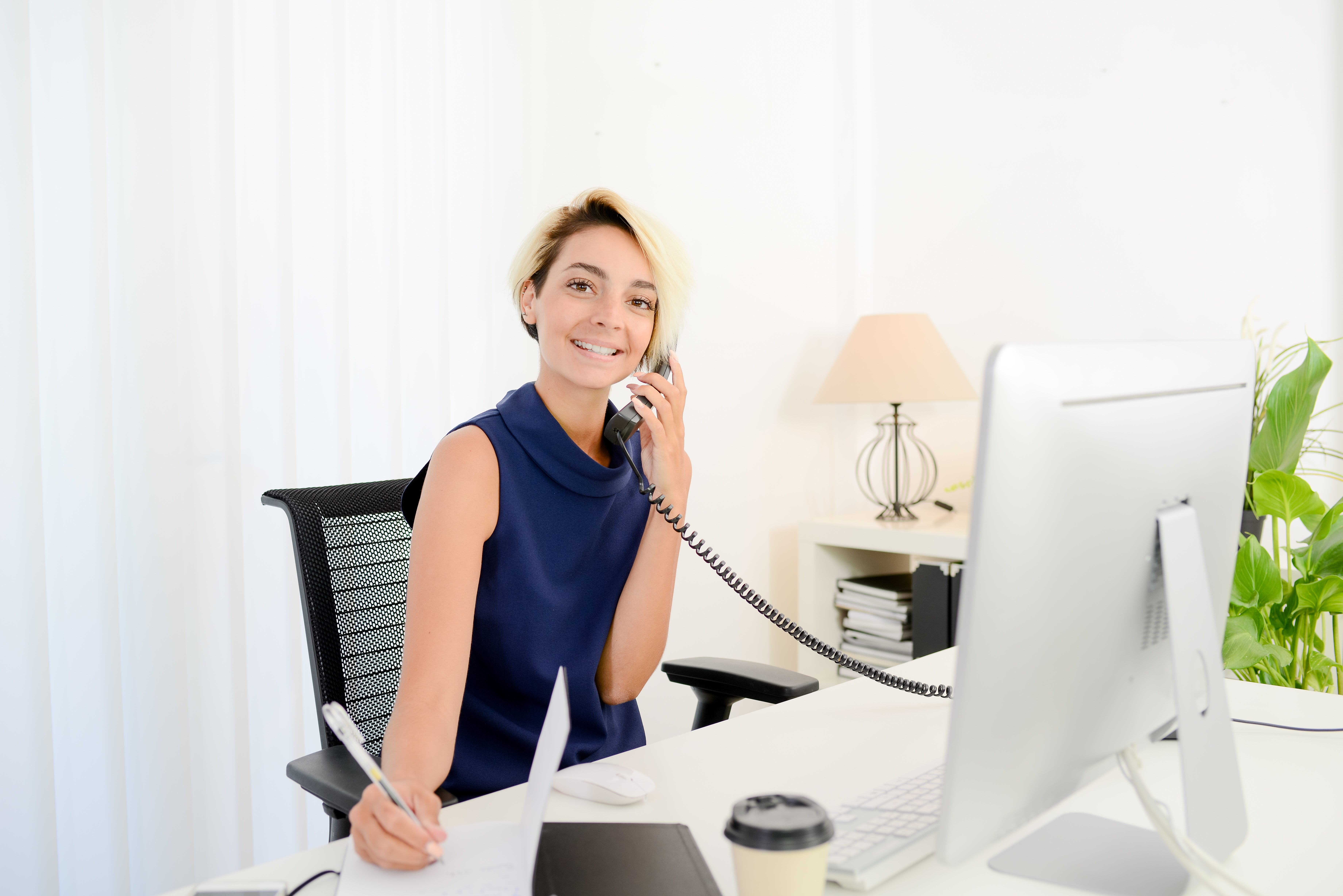 beautiful young business woman working at desk in white and bright office